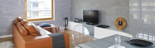 Skórzana kanapa i szare ściany w aranżacji salonu