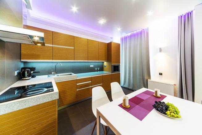 Mały salon z aneksem kuchennym – klasyczna aranżacja z różowym akcentem